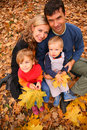 Family of four with yellow maple leaves in wood Royalty Free Stock Photo