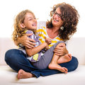 Family fun at home lovely girl and mother having laughing on sofa Stock Images