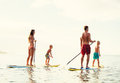 Family fun stand up paddling having together in the ocean on beautiful sunny morning Royalty Free Stock Image