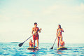 Family fun stand up paddling having together in the ocean on beautiful sunny morning Royalty Free Stock Photos
