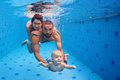Family fun in swimming pool - mother, father, baby dive underwater
