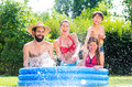 Family in garden pool cooling down splashing water by Royalty Free Stock Photos