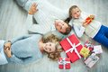 Family with giftboxes happy lying on the floor and looking at camera Royalty Free Stock Photography