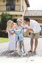 Family WIth Girl Riding Bike & Happy Parents Royalty Free Stock Photo