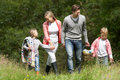 Family going on picnic in countryside walking towards camera Royalty Free Stock Images