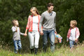 Family going on picnic in countryside walking towards camera Royalty Free Stock Photo