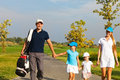 Family of golf players walking Royalty Free Stock Photo
