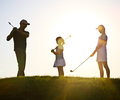 Family of a golfers at sunset Royalty Free Stock Photo