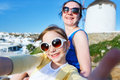 Family in greece happy mother and her adorable little daughter on vacation taking selfie at little venice area on mykonos island Stock Photo