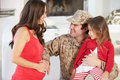 Family greeting military father home on leave smiling to each other and Royalty Free Stock Images