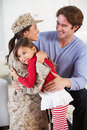 Family greeting military mother home on leave hugging and Royalty Free Stock Photos