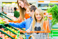 Family grocery shopping in hypermarket selecting fruits and vegetables while supermarket Royalty Free Stock Image