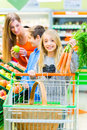 Family grocery shopping in hypermarket selecting fruits and vegetables while supermarket Stock Photos