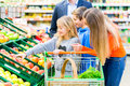 Family grocery shopping in hypermarket supermarket selecting fruits while Royalty Free Stock Photo