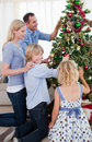 Family hanging decorations on a Christmas tree Stock Photos