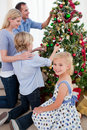 Family hanging decorations on a Christmas tree Stock Image