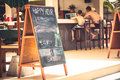 Family during happy hours at tropical beach cafe with signboard during summer beach holidays