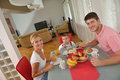 Family have healthy breakfast at home happy young kitchen with red details on bright morning light Stock Image