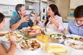 Family having argument sitting around table eating meal in kitchen shouting Stock Photo