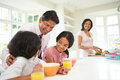 Family having breakfast before father leaves for work smiling at each other Royalty Free Stock Photography