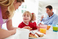 Family having breakfast in kitchen before school looking at each other smiling Stock Photos
