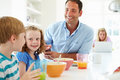 Family having breakfast in kitchen together eating cereal and drinking orange juice Stock Photos