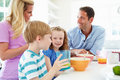 Family having breakfast in kitchen together looking at each other smiling Royalty Free Stock Images