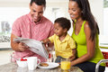Family having breakfast in kitchen together smiling to camera Stock Photos