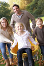 Family having fun with autumn leaves in garden Stock Images