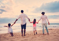 Family having fun on beach at sunset happy young Stock Photography