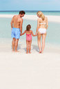 Family having fun in sea on beach holiday holding hands Stock Photo