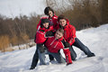 Family is having fun in the snow a red jackets wrestling playfully Royalty Free Stock Photos