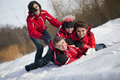 Family is having fun in the snow a red jackets wrestling playfully Royalty Free Stock Photo