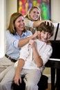 Family having fun teasing teenage boy at home