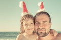 Family having fun at the tropical beach funny closeup portrait of dad with baby in santa hats xmas holidays concept Stock Photo