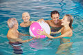 Family having fun with water ball happy in swimming pool in summer Stock Image