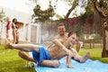 Family Having Fun On Water Slide In Garden Royalty Free Stock Photo