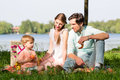 Family having picnic at lake sitting on meadow Royalty Free Stock Photo