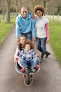 Family Having Ride In Wheelbarrow In Countryside Royalty Free Stock Photos