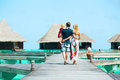 Family having tropical vacation from back view at maldives walking towards water bungalows Stock Image