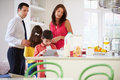 Family helping to clear up after breakfast looking at digital tablet Royalty Free Stock Image