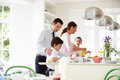 Family helping to clear up after breakfast smiling Royalty Free Stock Photos