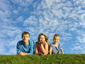 Family on herb under blue cloud sky Royalty Free Stock Photo