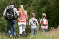 Family hiking in countryside rear view of Royalty Free Stock Photos