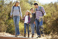 Family hiking in countryside wearing backpacks smiling Royalty Free Stock Photo