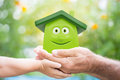 Family holding eco cartoon house hands against green spring background environment protection concept Royalty Free Stock Images