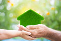 Family holding grass house hands against green spring background Stock Photo