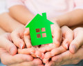 Family holding green paper house in hands real estate concept Stock Photography