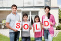 Family holding a sold sign outside their home Royalty Free Stock Photo