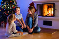 Family at home on christmas eve mother and her two little kids sitting by a fireplace in their Royalty Free Stock Images